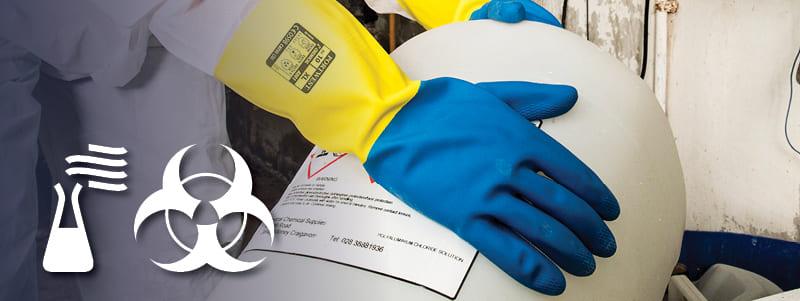 Trabajador con guantes Portwest resistentes a productos químicos manipulando artículos peligrosos.